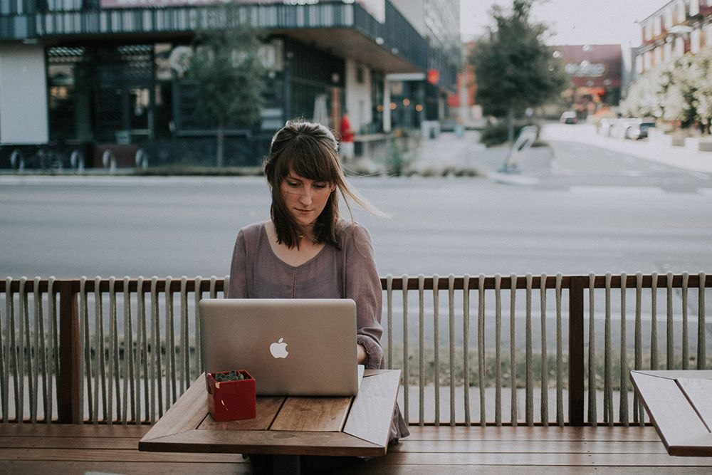 Woman comfortably working remotely outside.