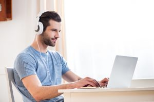 guy wearing headphones using the laptop
